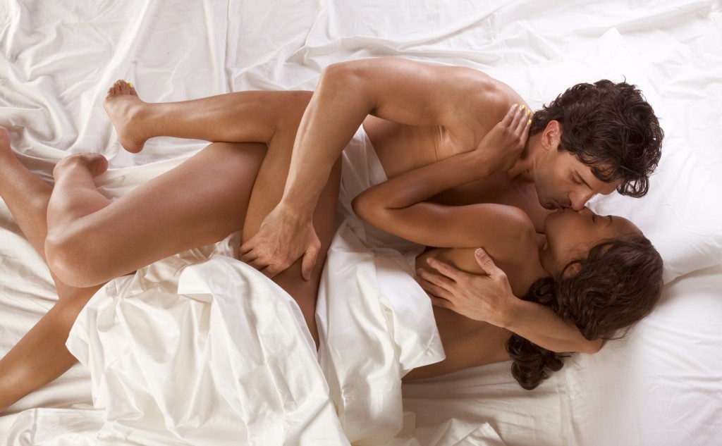 Loving affectionate nude heterosexual couple in bed engaging in sexual games, hugging and kissing. Mid adult Caucasian men in late 30s and young black African-American woman in 20s